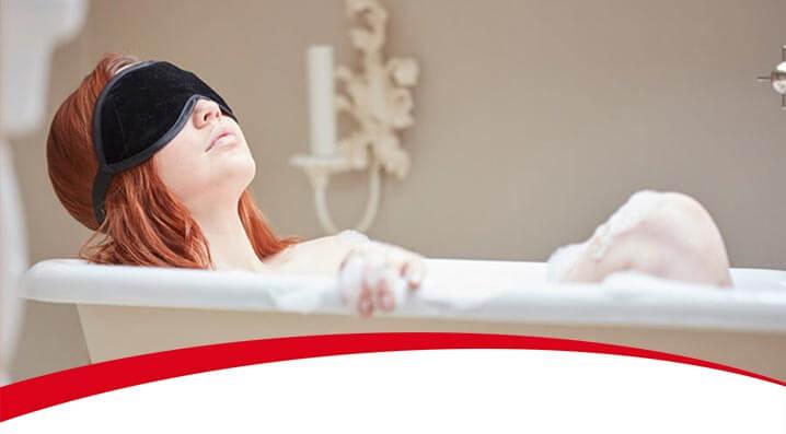 Frau mit Maske in der Badewanne